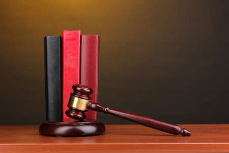 Judges gavel and books on wooden table on brown background photo