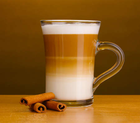 Fragrant coffee latte in glass cup and cinnamon on wooden table on brown background photo
