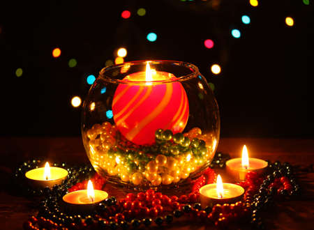 Wonderful composition with candle in glass on wooden table on bright background photo