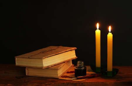 old books, scrolls, ink pen inkwell and candles on wooden table on black background photo