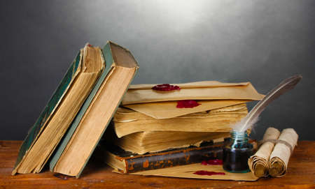 old books, scrolls, feather pen and inkwell on wooden table on grey background Stock Photo - 12553105