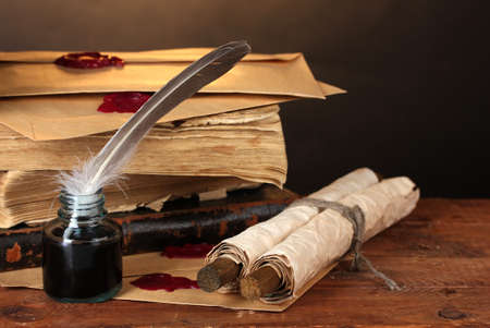 inkstand: old books, scrolls, feather pen and inkwell on wooden table on brown background