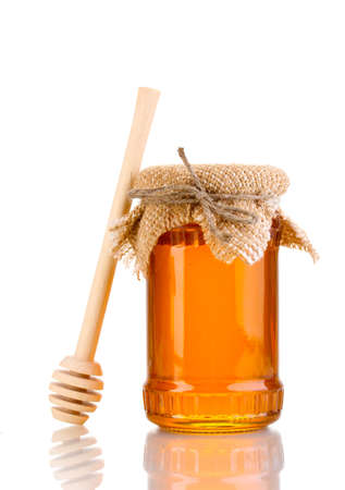 wooden spoon: Sweet honey in jar with drizzler isolated on white