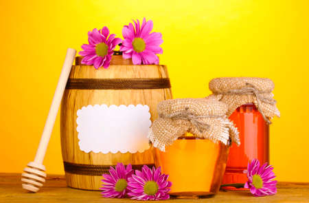 Sweet honey in jars and barrel with drizzler on wooden table on yellow background photo