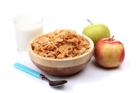 tasty cornflakes in wooden bowl, apples and glass of milk isolated on white photo