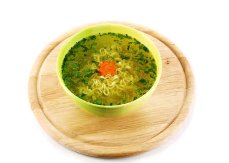 Tasty soup on wooden round board isolated on white photo
