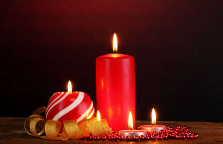 Wonderful candles on wooden table on dark background photo