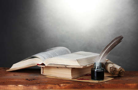 ancient book: old books, scrolls, feather pen and inkwell on wooden table on grey background Stock Photo