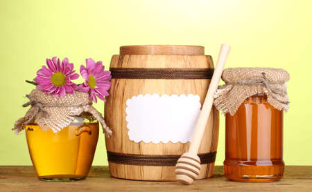 Sweet honey in jars and barrel with drizzler on wooden table on green background photo