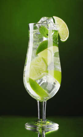 glass of cocktail with lime and mint on green background photo