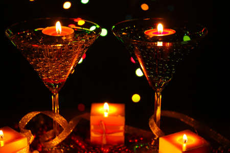 Amazing composition of candles and glasses on wooden table close-up on bright background photo