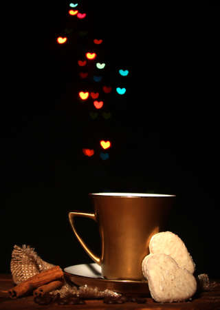 valentinas: golden cup of coffee on wooden table on bright bokeh backdground