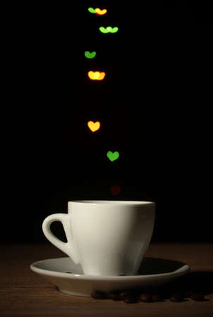 cup of coffee on wooden table on bright bokeh backdground photo