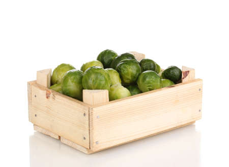 Brussels sprouts in wooden crate isolated on white photo