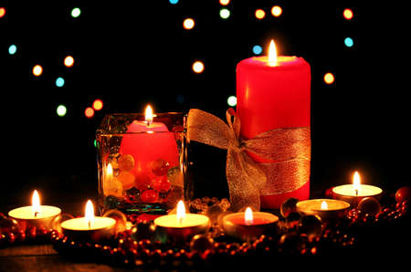 Wonderful composition of candles on wooden table on bright background photo