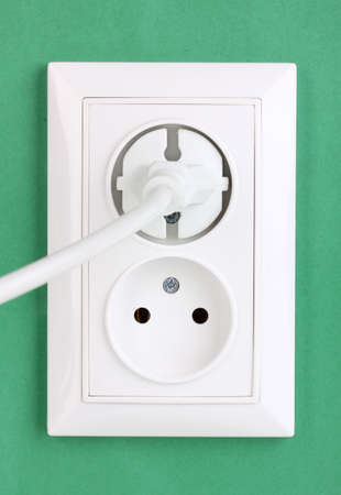 White electric socket with plug on the wall Stock Photo - 12553252
