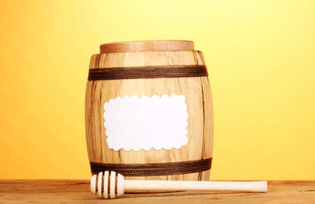 Sweet honey in barrel with drizzler on wooden table on yellow background Stock Photo - 12549759