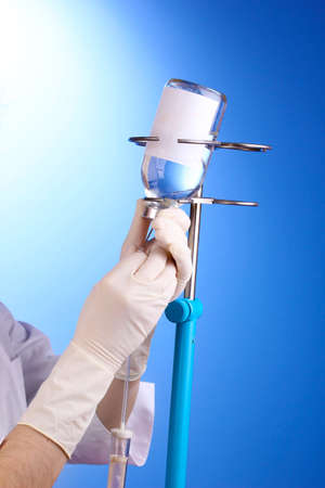 intravenously: Nurse doing infusion on blue background
