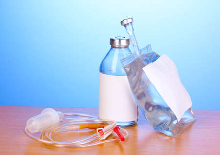 Bottle and bag of intravenous antibiotics and plastic infusion set on wooden table on blue background photo