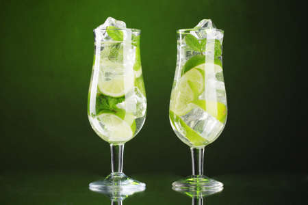 glasses of cocktails with lime and mint on green background photo