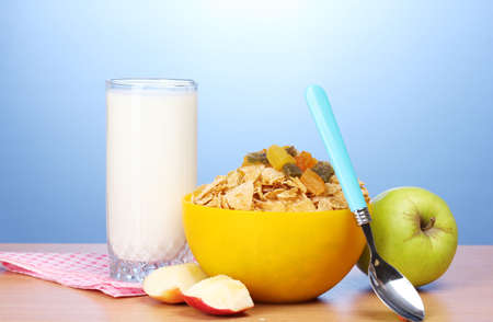 tasty cornflakes in yellow bowl, apples and glass of milk on wooden table on blue background Stock Photo - 12562583