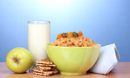 tasty cornflakes in green bowl, apples and glass of milk on wooden table on blue background Stock Photo - 12562603