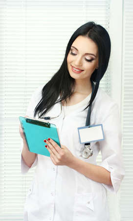 young beautiful doctor handing folder and write photo