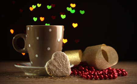 valentinas: cup of coffee on wooden table on bright bokeh backdground
