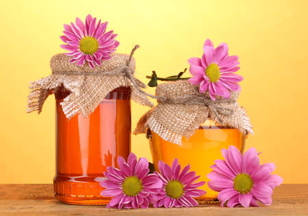 Sweet honey in jars on wooden table on yellow background photo