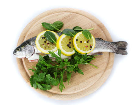 Fresh fish with lemon, parsley and pepper on wooden cutting board isolated on white  photo