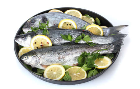 Fresh fishes with lemon, parsley and pepper on plate isolated on white photo