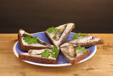 Tasty sandwiches with sprats on plate on wooden table on brown background photo