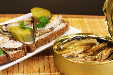 sprats: Tasty sandwiches with sprats on plate on wooden mat on brown background Stock Photo