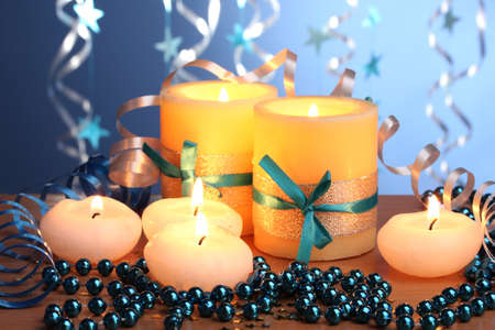 Beautiful candles, gifts and decor on wooden table on blue background Stock Photo - 12633770