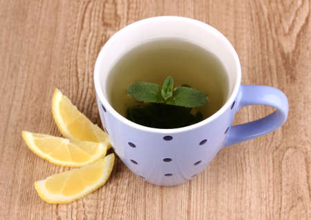 english breakfast: Mint tea with mint leaf and lemon on wooden background