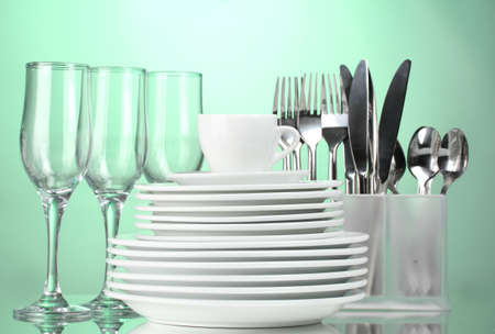 clean dishes: Clean plates, glasses, cup and cutlery on green background Stock Photo