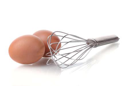 kitchen utensils: Metal bata para batir los huevos y los huevos marrones aislados en blanco Foto de archivo