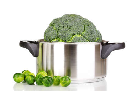 Fresh broccoli in saucepan and brussels sprouts isolated on white photo