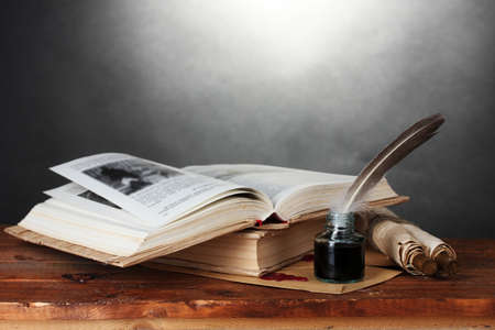 old books, scrolls, feather pen and inkwell on wooden table on grey background Stock Photo - 12649663