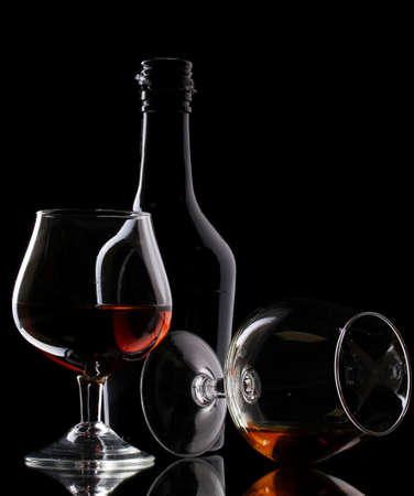 whisky: Glasses of brandy and bottle on black background Stock Photo