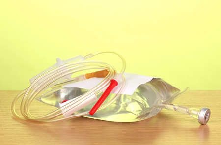Bag of intravenous antibiotics and plastic infusion set on wooden table on green background photo