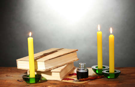 old books, scrolls, ink pen inkwell and candles on wooden table on grey background Stock Photo - 12649497