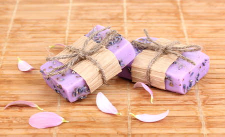 Hand-made lavender soaps on wooden mat photo