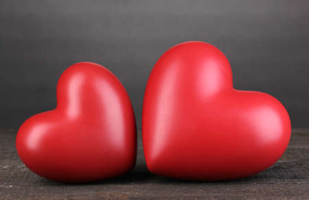 Two decorative red hearts on wooden table on grey background photo