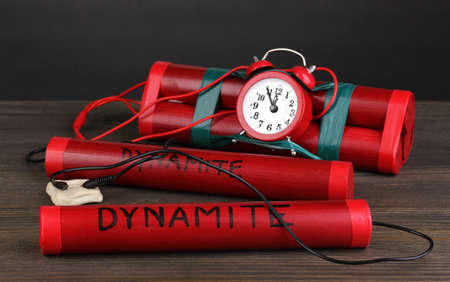 Timebomb made of dynamite on wooden table on grey background photo