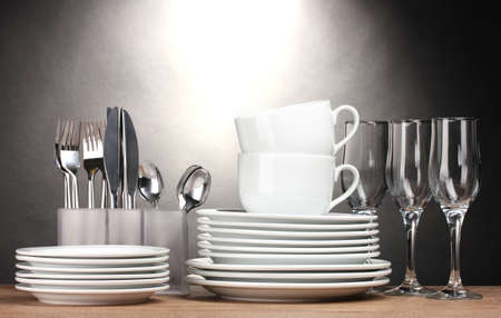 Clean plates, glasses, cups and cutlery on wooden table on grey background photo