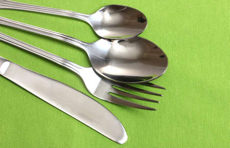 Fork, spoon and knife on a green tablecloth photo