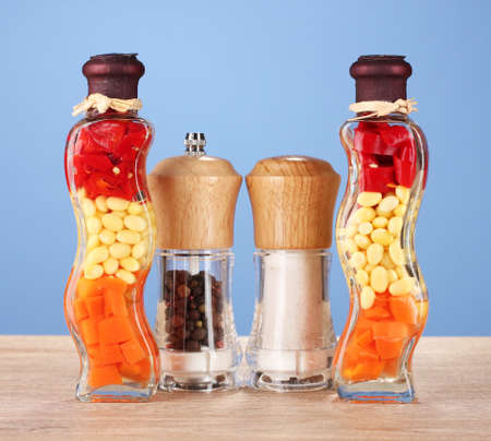Two bottles with red pepper, beans, carrots for kitchen decor with salt and peper on blue background