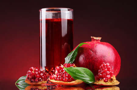 pomergranate: ripe pomergranate and glass of juice on red background Stock Photo