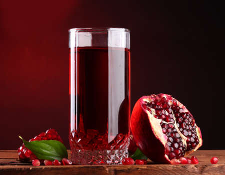 ripe pomergranate and glass of juice on wooden table on red background photo